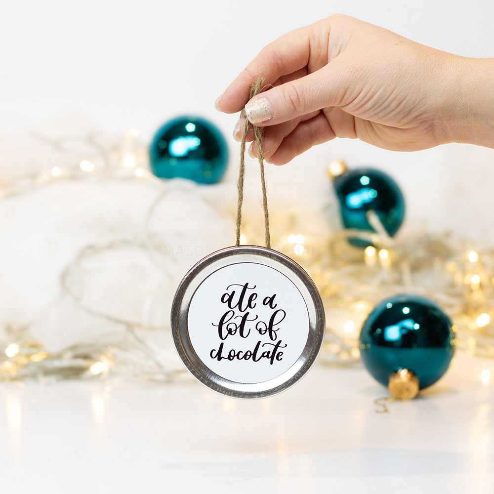 "A hand holds a gold mason jar lid Christmas ornament that says ""ate a lot of chocolate"" in black cursive on a white background. In the background of the picture are teal ball ornaments and white Christmas lights"