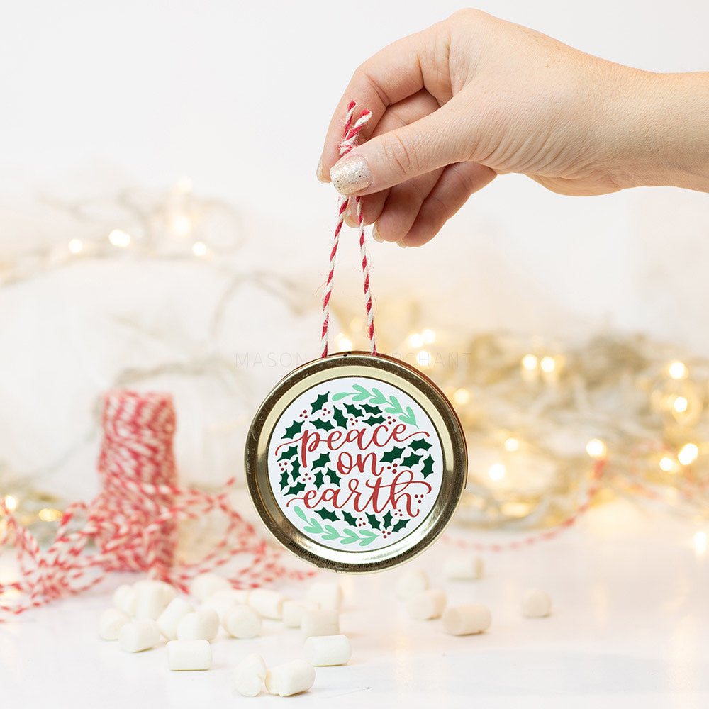 "A hand holds a gold mason jar lid Christmas ornament that says ""peace on earth"" in red cursive text on a white background with green holly leaves. In the background of the picture are marshmallows, red and white string and some white Christmas lights"