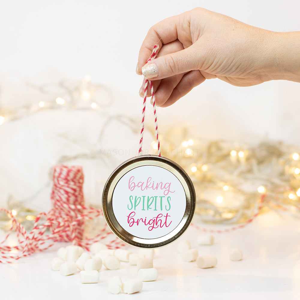 "A hand holds a gold mason jar lid Christmas ornament that says ""baking spirits bright"" in pink and green cursive text on a white background. In the background of the picture are marshmallows, red and white string and some white Christmas lights"
