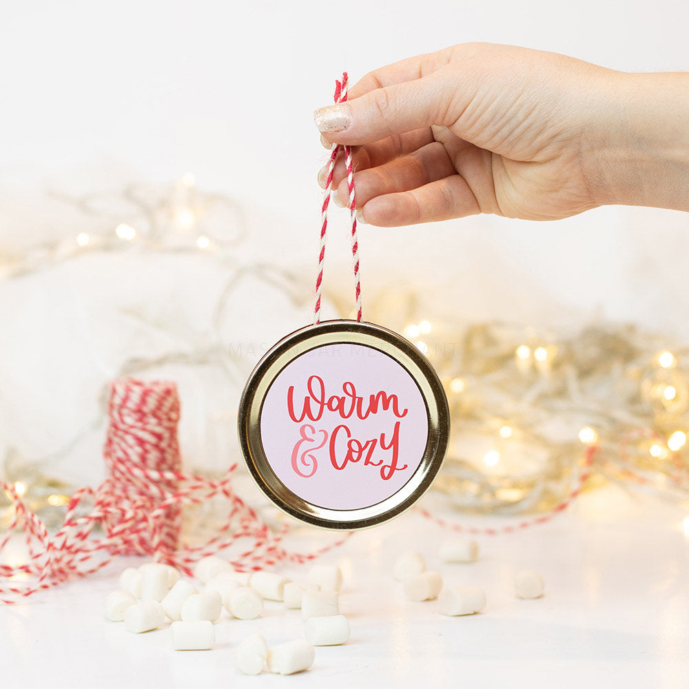 "A hand holds a gold mason jar lid Christmas ornament that says ""warm & cozy"" in pink and red cursive text on a white background. In the background of the picture are marshmallows, red and white string and some white Christmas lights"