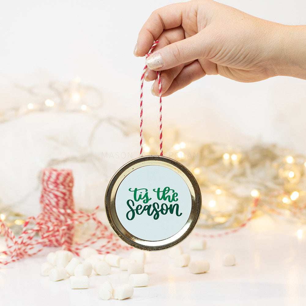 "A hand holds a gold mason jar lid Christmas ornament that says ""tis the season"" in green cursive text on a white background. In the background of the picture are marshmallows, red and white string and some white Christmas lights"