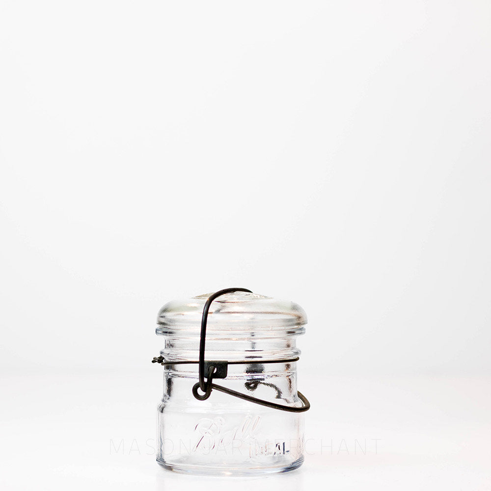 Vintage 1920s almost half-pint wire bail Ball mason jar against a white background