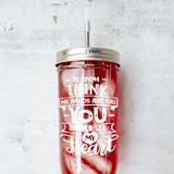 "Mason Jar Tumbler with Stainless Steel Straw on concrete counter that reads ""If you think my hands are full you should see my heart"" In white"
