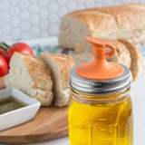 Orange Jarware Mason Jar Oil /Vinegar Cruet shown on a white countertop with a loaf of fresh baked bread in the background.