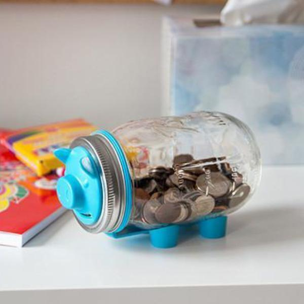 16 oz reusable glass mason jar with a silver and blue piggy bank lid. The jar is on its side and made to look like a pig