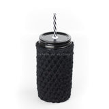 24 oz reusable glass mason jar tumbler with an all black straw lid and a black and white stripped reusable straw. A black knit cozy covers the jar