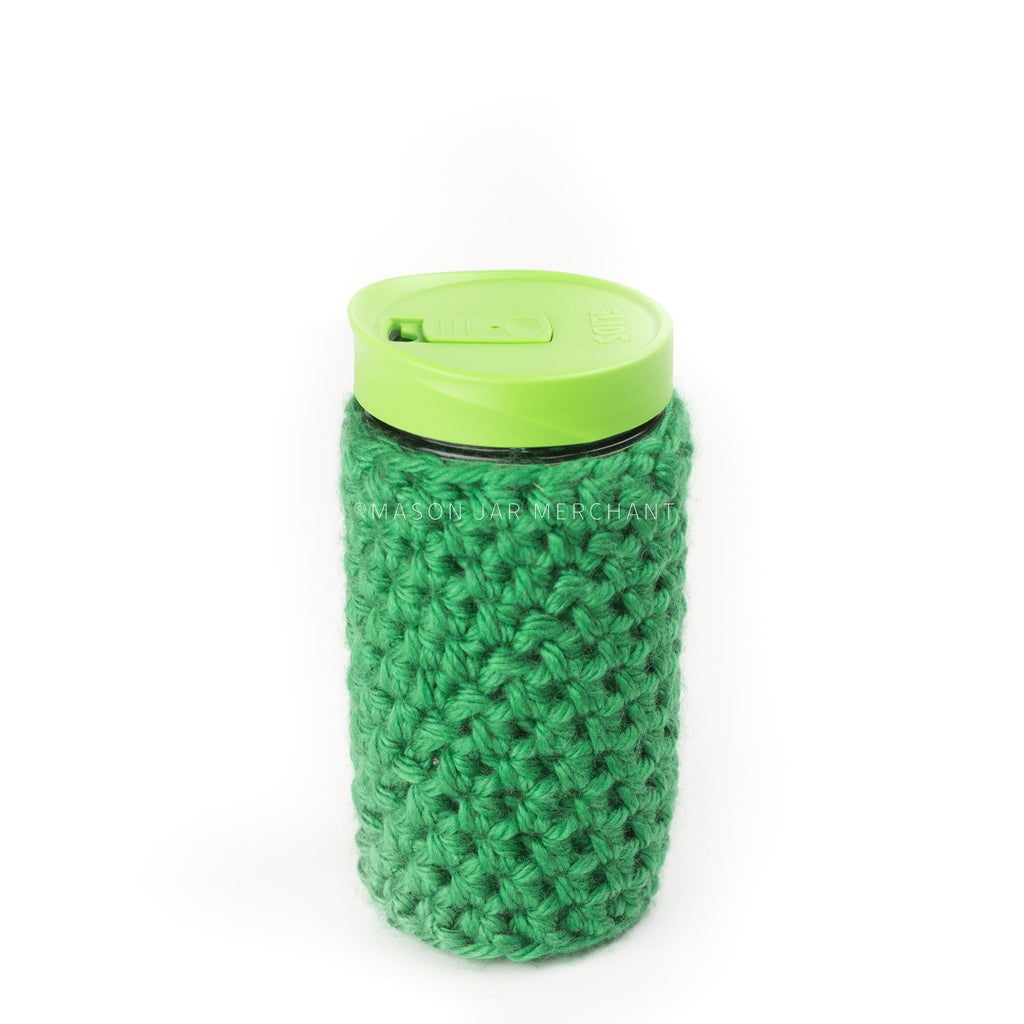 24 oz reusable glass mason jar tumbler with a green sippy cup lid. A green knit cozy covers the jar