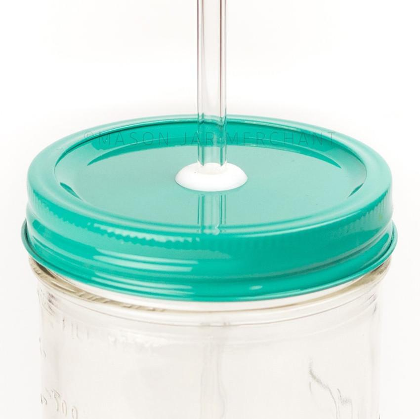 Close-up of a 24 oz mason jar with a turquoise custom painted lid with a white silicone grommet and a glass straw, against a white background