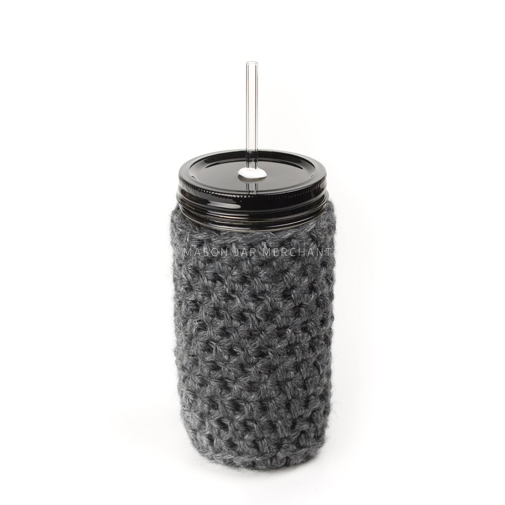 24 oz reusable glass mason jar tumbler with an all black straw lid and a glass reusable straw. A black knit cozy covers the jar