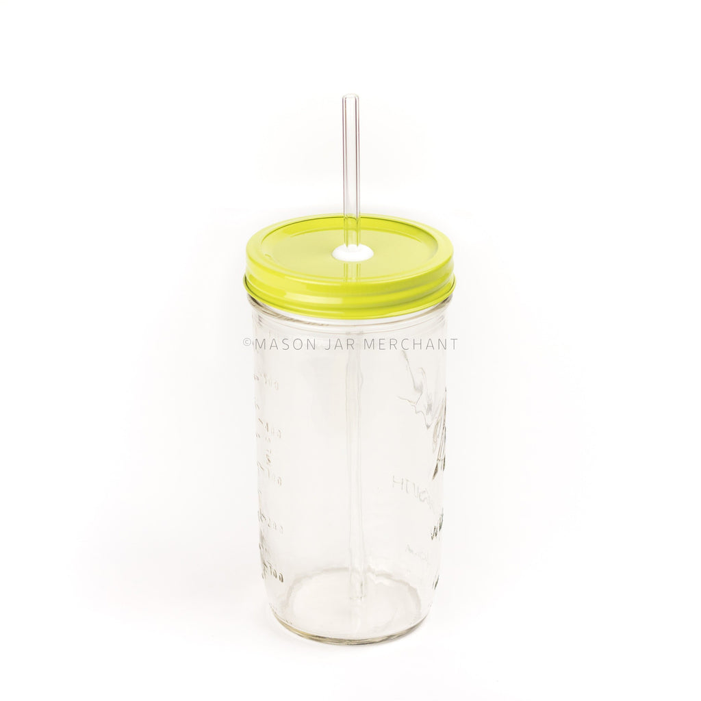 A 24 oz mason jar with a chartreuse custom painted lid with a white silicone grommet and a glass straw, against a white background