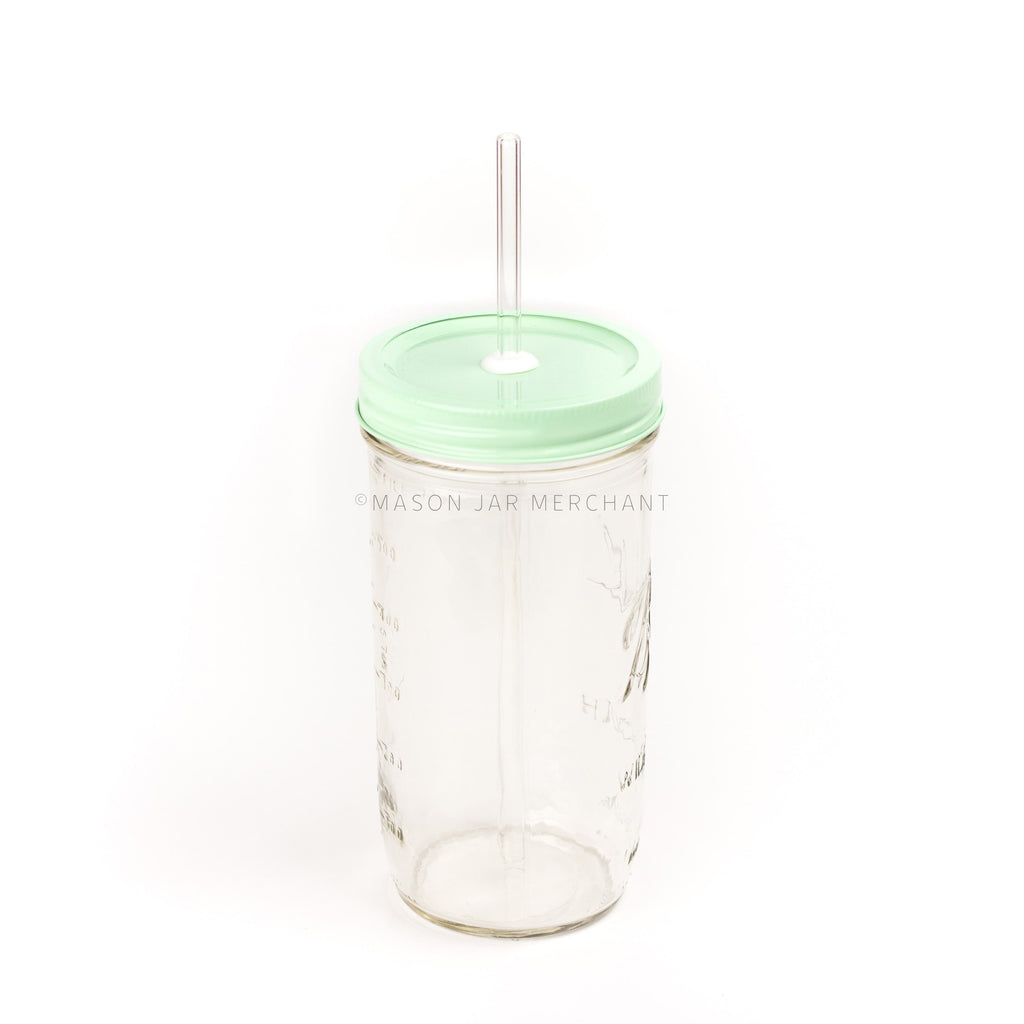 A 24 oz Ball mason jar with an aqua coloured custom painted lid with a white silicone grommet and a glass straw, against a white background