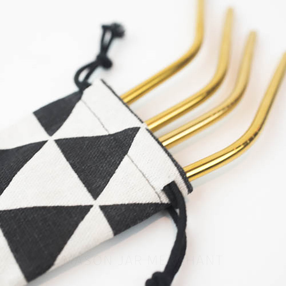Close-up of a triangle pattern reusable straw bag and gold stainless straws