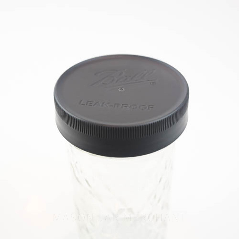 Close-up of a Ball brand regular mouth mason jar storage lid on a mason jar against a white background