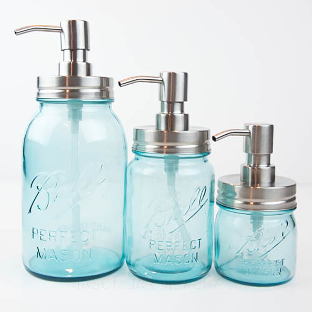 Three blue ball mason jar soap dispensers stand in a line on a white background. One is 32 oz, 16 oz and 8 oz