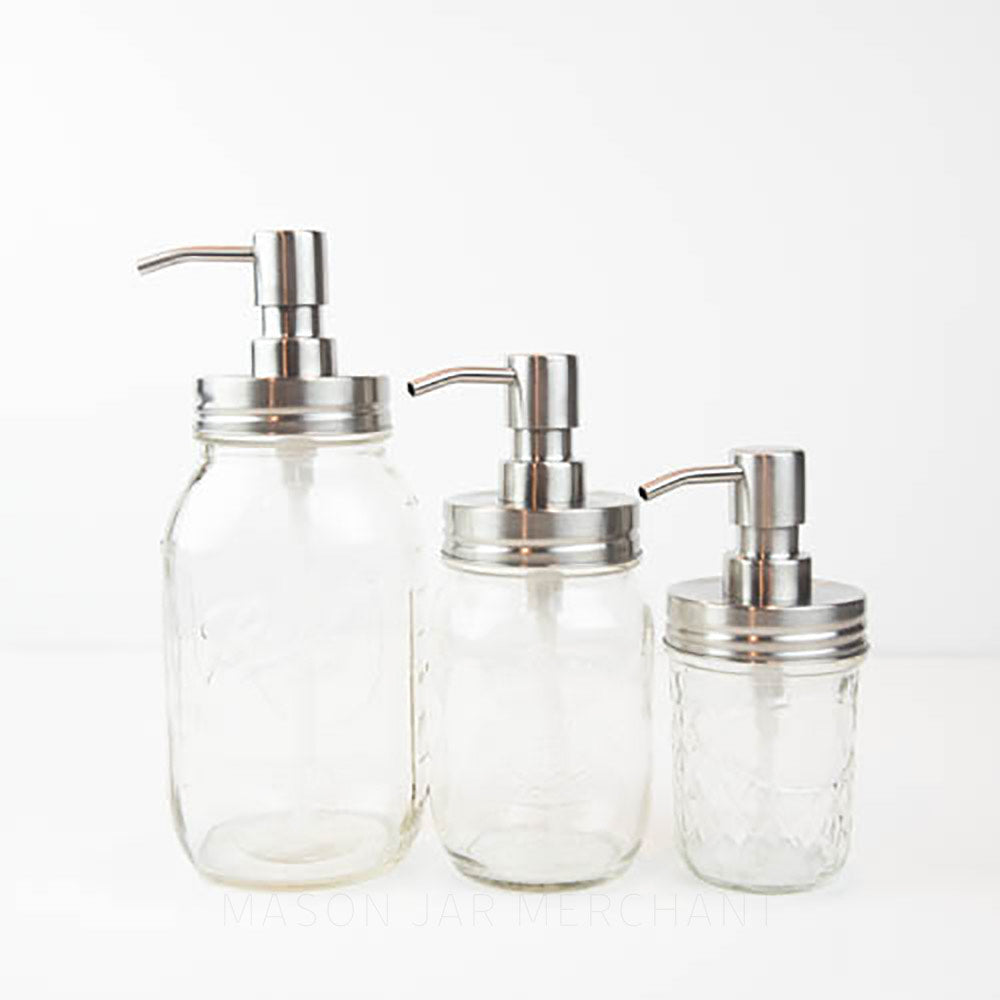 Three glass reusable mason jar soap dispensers stand in a line on a white background. One is 32 oz, 16 oz and 8 oz