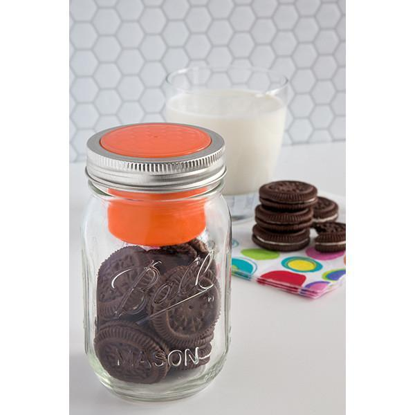 Orange Jarware Snack Cup shown on a Regular Mouth Pint jar on a white countertop with chocolate cookies.