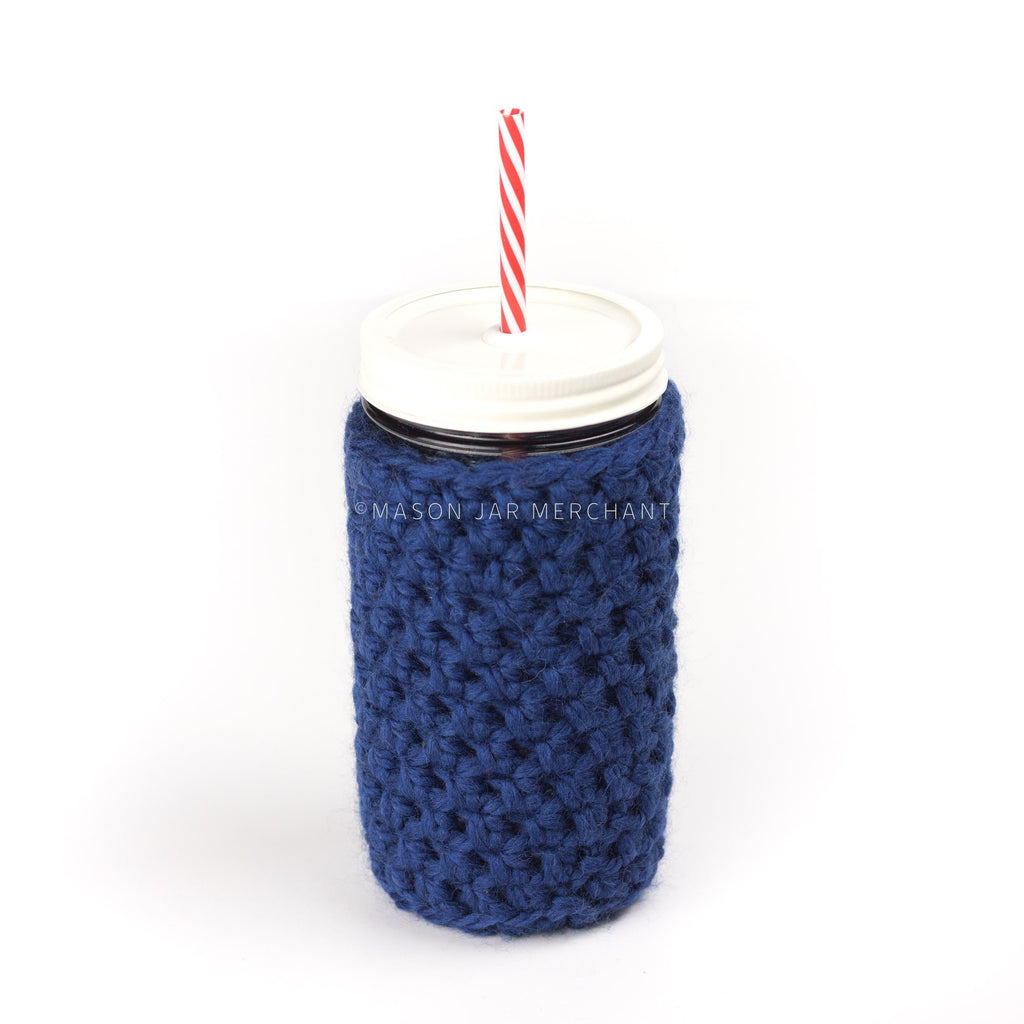 24 oz glass reusable mason jar tumbler with an all white painted straw lid and a red and white stripped reusable straw. A navy blue knit cozy covers the jar