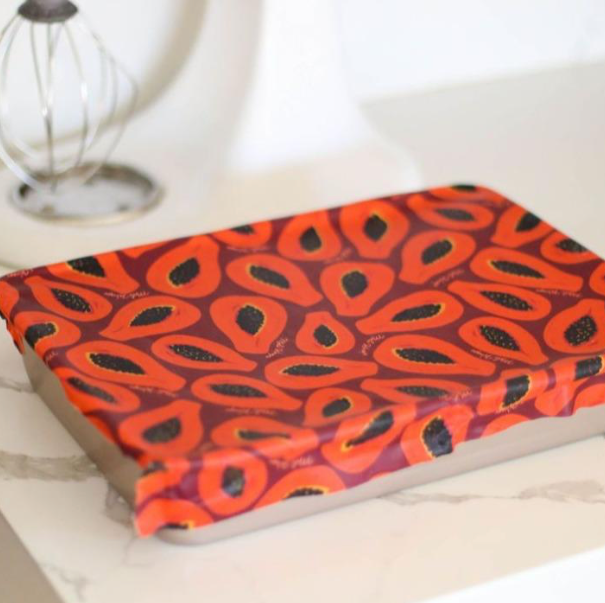 Some reusable wax food wrap in purple papaya print covers a silver pan that sits on a white marble kitchen counter