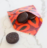 a piece of reusable wax food wrap in purple papaya print in the shape of an envelope is filled with Oreos. It all sits on a white marble counter top