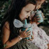 Two little girls drink out of a mason jar silicone squeeze pouch jar with a grey plastic ring and an aqua straw lid
