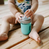 A small child sits behind a glass reusable mason jar bottle with an aqua silicone sleeve, a plastic mason jar ring and a rubber bottle top