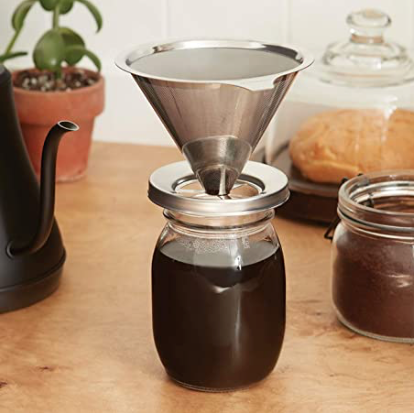 A jarware stainless steel mason jar pour over set sits on top of a glass reusable mason jar with coffee in it. In the background is a black kettle, a container of coffee, some bread and a plant sits on a kitchen counter