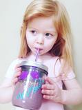 "a little girl sips on a 16 oz reusable glass mason jar tumbler with a silver straw lid and a purple and white stripped reusable straw. on the jar are the words ""I'd rather be"" in gold block text and ""mermaid"" in teal cursive, above it are two purple shells"