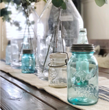 A variety of mason jars on a table, including a blue Ball mason jar with a zinc lid in the foreground