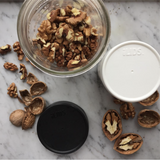 black and white storage lids sit on a counter with a glass jar full of nuts