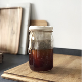 32 oz glass reusable mason jar sits on a wooden cutting board on a kitchen counter. The jar is filled with coffee and has a coffee filter with coffee ground in it