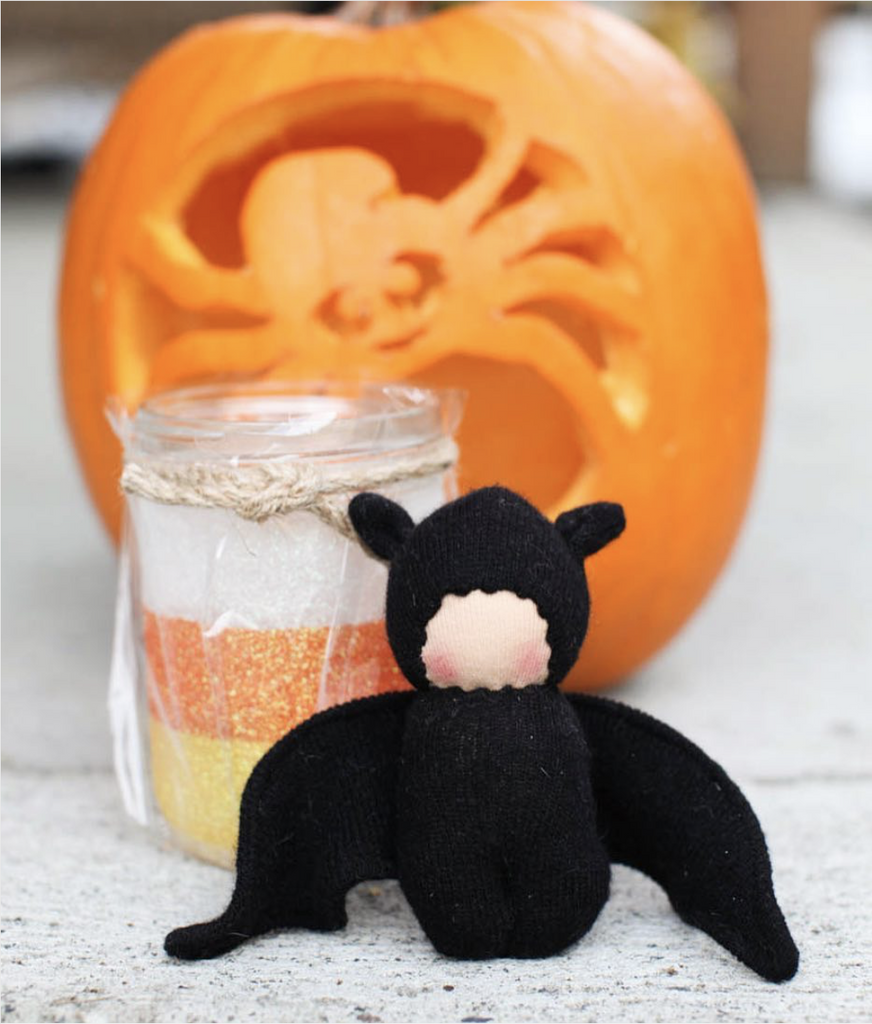 a white, orange and yellow glitter glass reusable mason jar sits in a clear bag, in front is a stuffed black bat and behind is an orange pumpkin with a spider carved into it