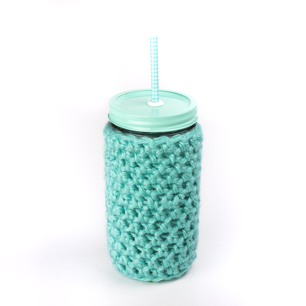 A 24 oz wide mouth mason jar with an aqua coloured custom painted lid, a glass straw, and a matching crocheted jar cozy against a white background