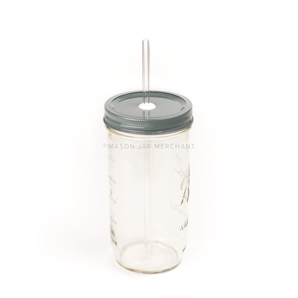 A 24 oz wide mouth mason jar with a dark gray custom painted lid with a white silicone grommet and a glass straw, against a white background