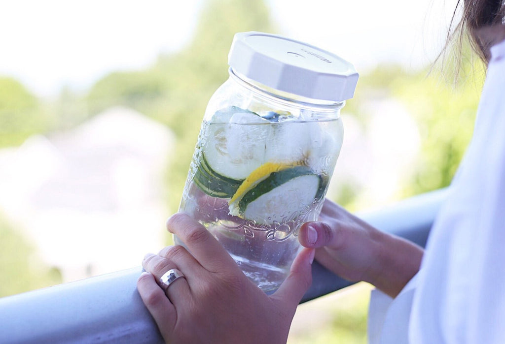 Woman is outdoors holding a quart size mason jar with lemon cucumber water in it with a white MasonTops tough top on the jar.