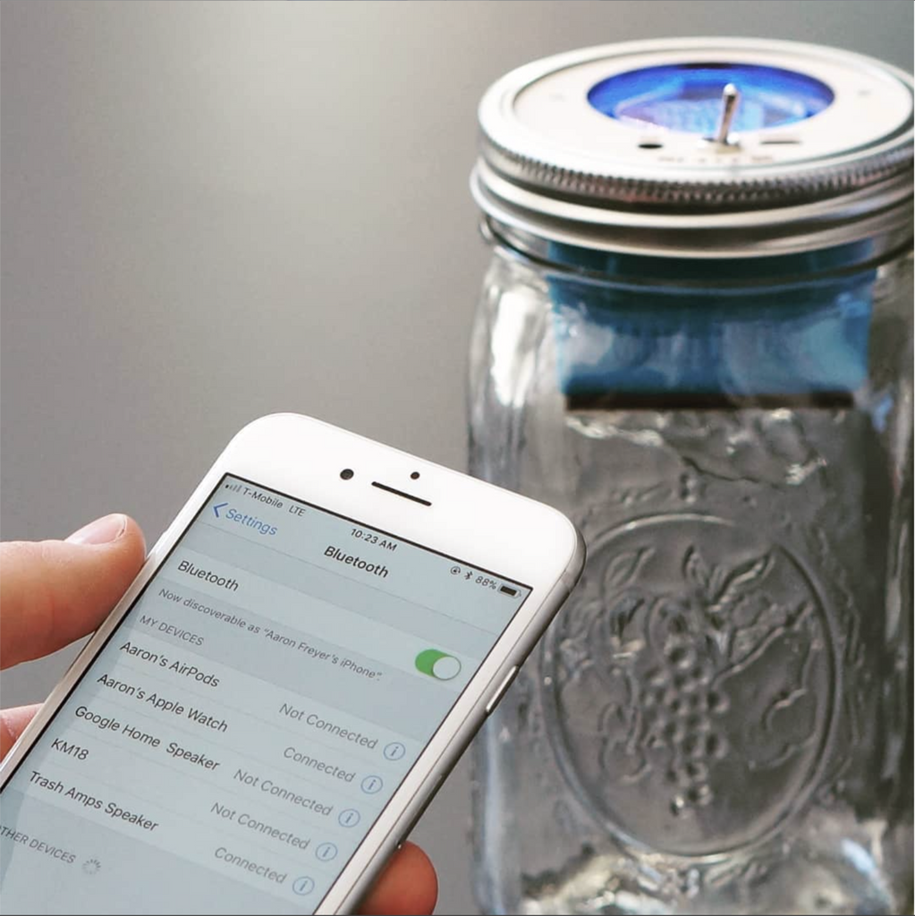 an iPhone on bluetooth with a speaker in a glass reusable mason jar in the background
