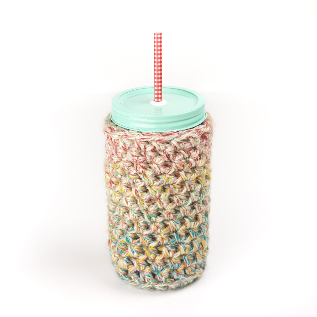 24 oz glass reusable mason jar tumbler with a light aqua painted straw lid and a red and white gingham reusable straw. An off white knit cozy with flex of red, yellow, teal and blue covers the jar