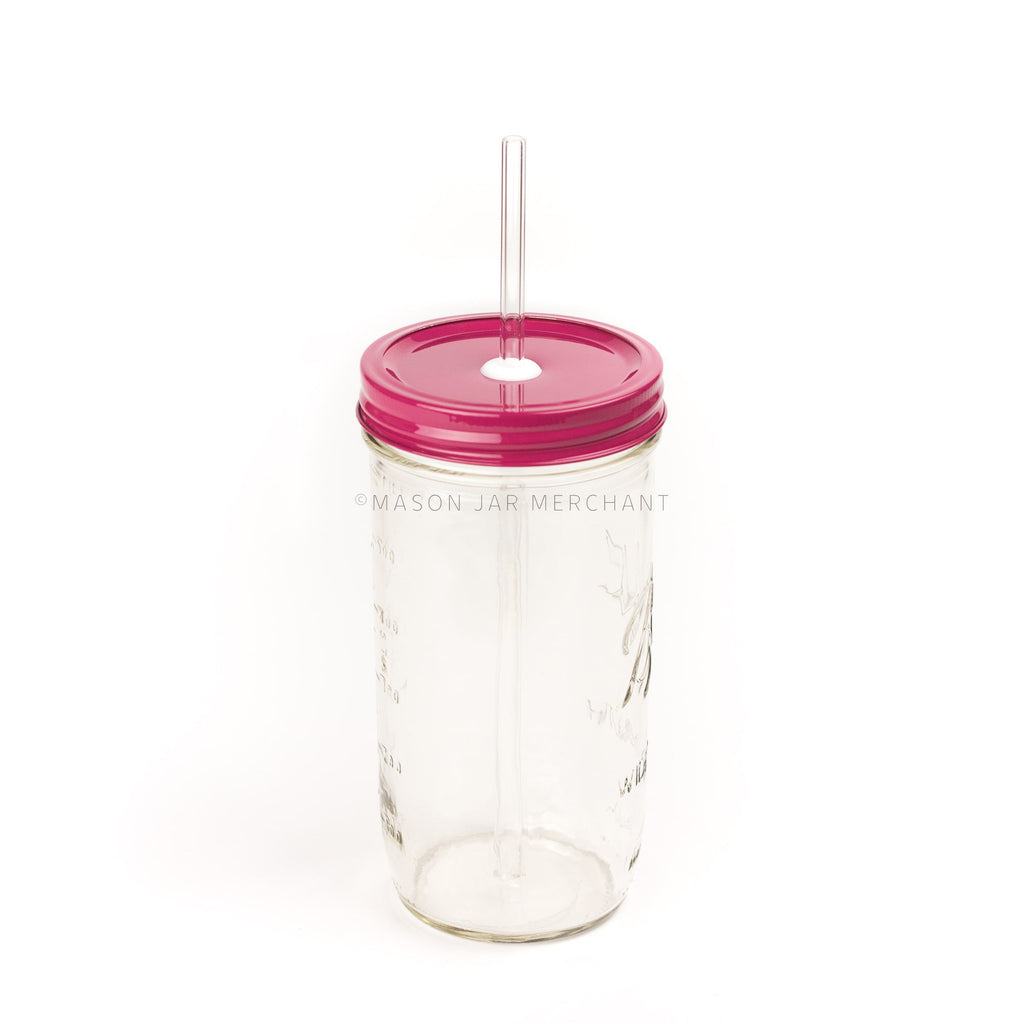 A 24 oz wide mouth mason jar with a fuchsia coloured custom painted lid with a white silicone grommet and a glass straw, against a white background