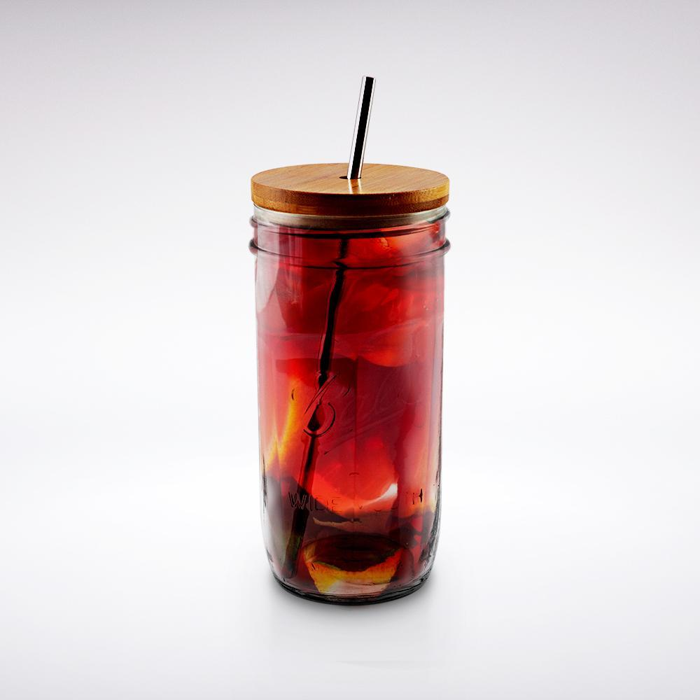24 oz reusable glass mason jar tumbler with handmade bamboo straw lid and stainless steel reusable straw, full of iced tea
