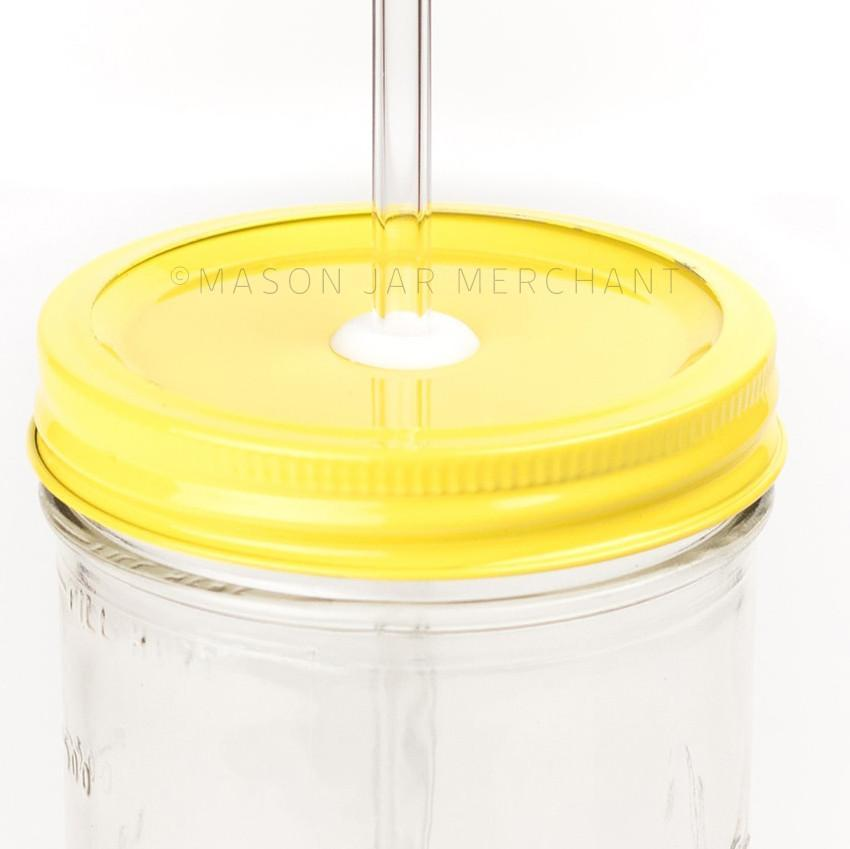 Close-up of a 24 oz wide mouth mason jar with a yellow custom painted lid with a white silicone grommet and a glass straw, against a white background