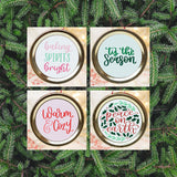 Set of 4 bright pink green and red script text mason jar lid Christmas ornaments on a background of green pine needle branches