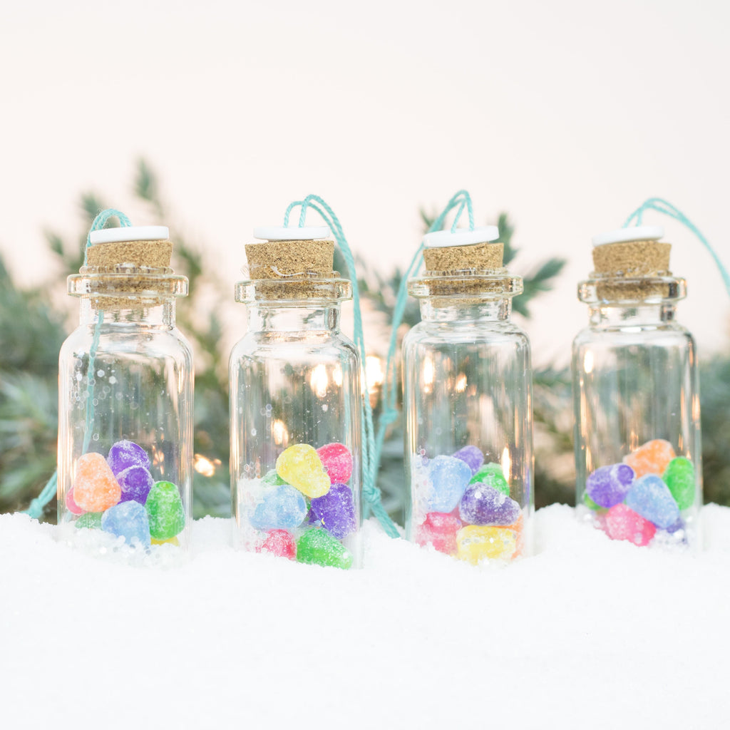 four glass jar ornaments with cork lids sit in a row on a pile of snow on a white and green background. In each jar is a bunch of rainbow coloured gumdrops