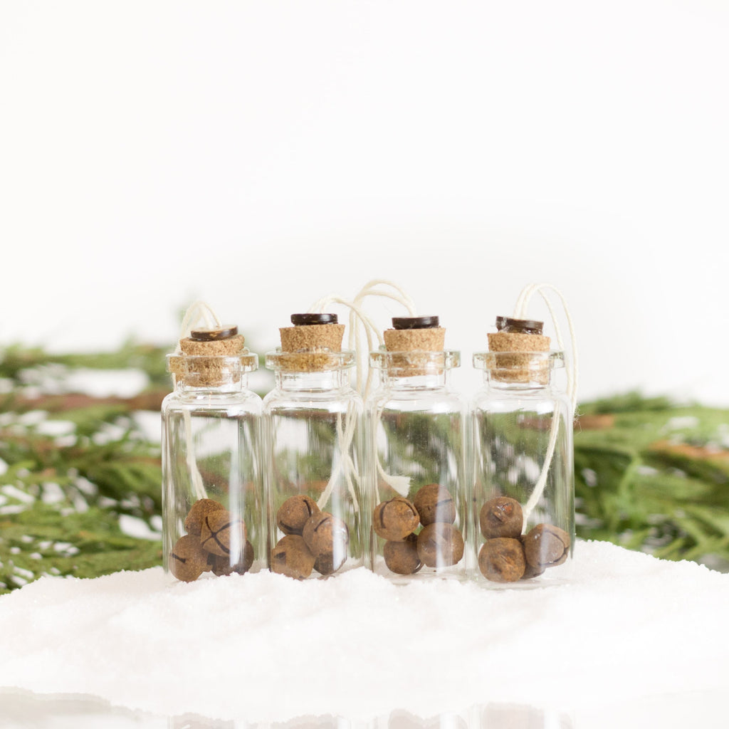 Four small jar ornaments sit in a pile of snow on a white and green background. In each jar are four rusty jingle bells
