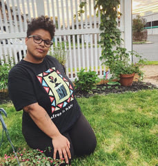 Melanie Lino in an AFros in Nature Teeshirt sitting on green grass looing sanguine