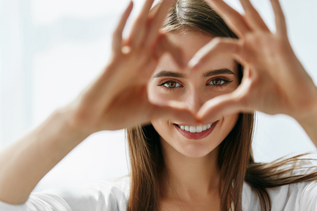 Woman holding heart hands in front of her face.