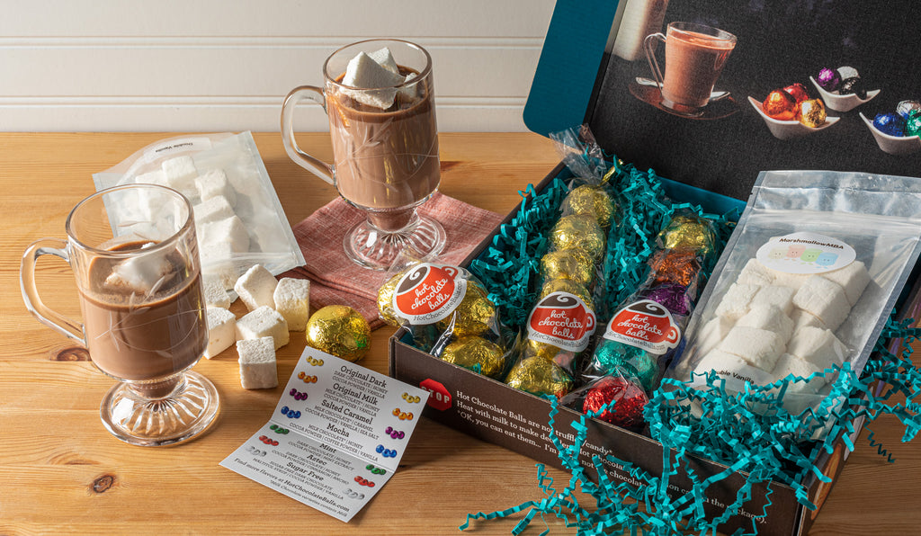 Giftbox with hot chocolate balls spilling out and homemade marshmallows. Shown with prepared hot chocolate in a mug.