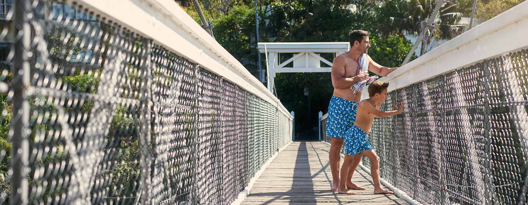 Tom and Teddy Sale - Shown with father and son on lighthouse next to the waterside and beach wearing our matching turtle print swim shorts