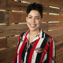 Photo of Jess smiling wearing a striped red and black shirt standing in front of wood panelling