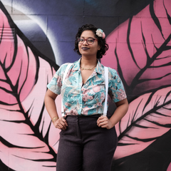 Photo of Chandrika wearing a blue shirt and suspenders standing in front of a wall with a pink leaf mural