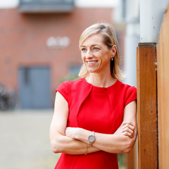 Photo of Breda wearing a red dress standing with her arms crossed smiling