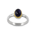 Ring in silver with a cabochon amethyst in a gold setting.